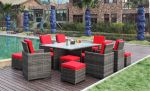 Hagemøbler i rotting som står ved et basseng på en utendørs plating. Røde puter i hagestolene. SparMax